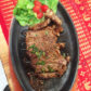 Rindssteak serviert auf heisser, gusseiserner Platte mit Beilage nach Wahl
